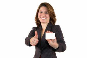 junge, lächelnde Geschäftsfrau mit business card mit Daumen hoch
