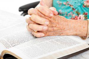 Praying Senior Hands on Bible