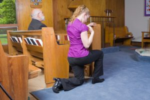 White woman crossing herself in a church aisle. Senior man sitting in pew.
