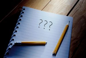 Three questions mark and broken pencil on top of a note pad