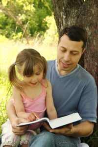 young father with a small daughter reading the Bible